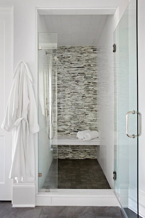 Luxurious walk-in shower design with linear mosaic glass tile shower surround and floating shower bench over dark gray shower floor.
