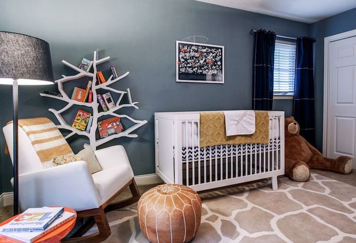 Adorable boy's nursery features blue walls accented with navy blue curtains, Land of Nod Blue Canvas Curtain Panels, as well as art over white crib, Oeuf Sparrow Crib, dressed in black and white chevron crib sheets, beside Land of Nod White Leather Joya Rocker accented with striped throw blanket paired with Land of Nod Light Years Grey Floor Shade and Graphite Base, West Elm Martini Side Table and brown leather Moroccan pouf situated in front of Nursery Works Tree Bookcase atop white and…