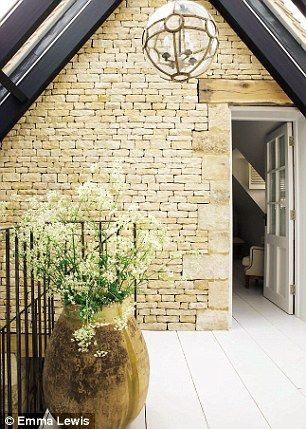 On the landing, the contemporary glass-vaulted roof is offset with Cotswold dry-stone wall...