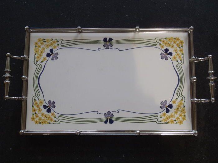 Prachtig dienblad met elegant gestileerd bloemenmotief van viooltjes en sleutelbloemen. Gave tegel en vernikkeld frame. Lichte gebruikssporen en een lichte vlek op het blad en wat slijtage aan het frame (zie foto's). Afmetingen: tegel 36x22 cm. Totale lengte inclusief handvaten 45 cm.