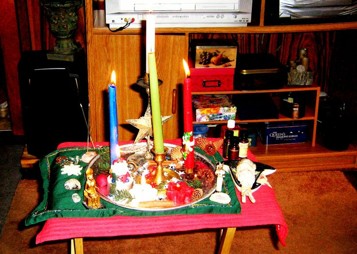 """Yule altar 2013 by Ruth Pace  As an eclectic solitary, I do things because they feel right for me. I follow some sort of structure that is taught - but then I adapt those things to what is in my heart.  I use a small portable folding wooden """"tv table"""". The red cloth is a novelty dishtowel and the green one is a beaded decorative accent pillowcase (I think I got it at Target some years ago). The center tray is a metal party tray (to catch wax)."""