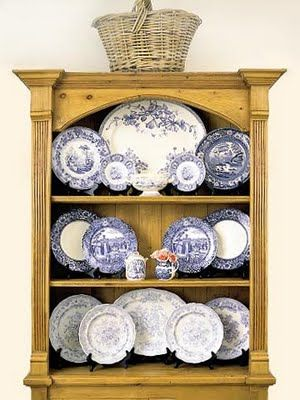 A wall mounted display cabinet shows off the blue and white china perfectly.