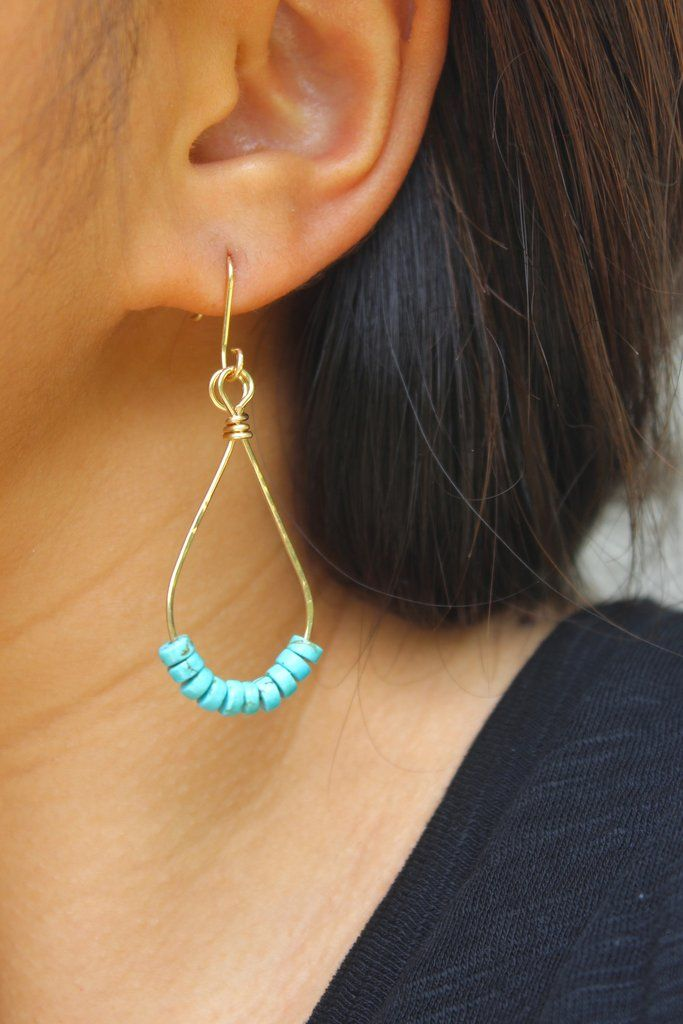 A pair of drop earrings that feature dyed turquoise beads. The turquoise beads are suspended from a teardrop-shaped 14K gold fill hoop. The earrings are hammered for strength and texture. All metal ha