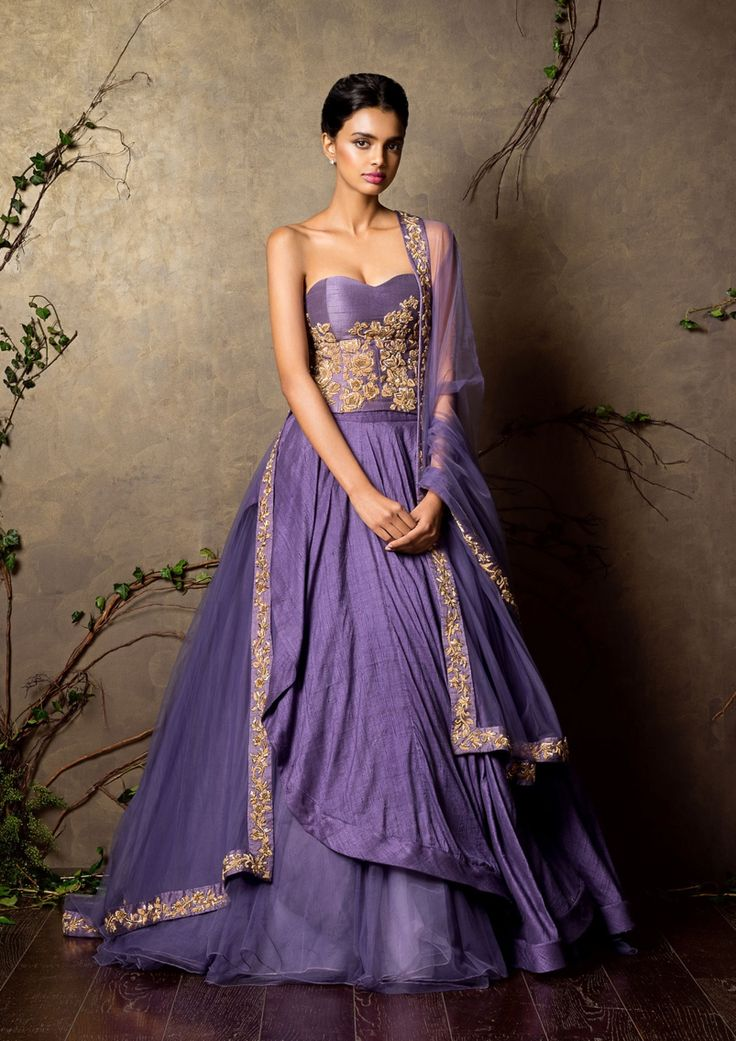 A patrician purple raw silk asymmetric flare lehenga teamed with a matching corset. This is worn with a tulle dupatta having ornate gold zardozi embroidery as seen on the corset.