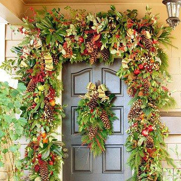 "We love this over-the-top front door design from Better Homes & Gardens. ""This large, leafy garland and matching front door swag is made from evergreen branches, pinecones, berries, apples, magnolia leaves, and festive holiday ribbon."" All of the elements can be purchased as faux greenery & fruits"