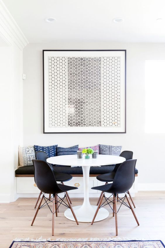 A chic, isolated dining space with tulip Saarinen style table and black molded plastic chairs.