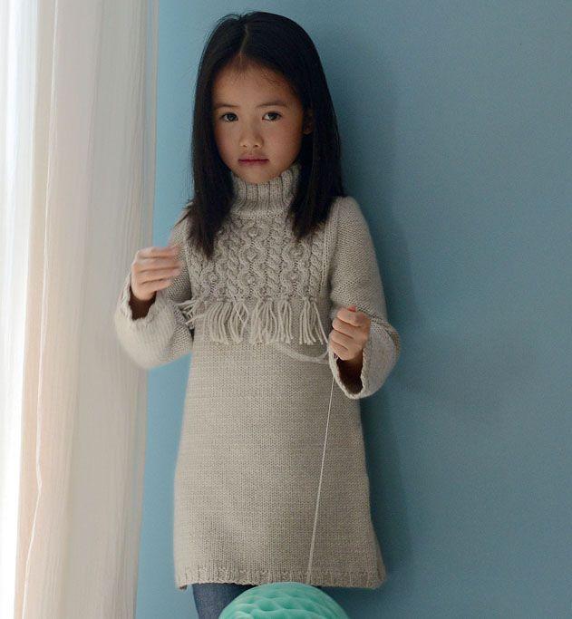 Amandine porte un pull allongé à franges tricoté en ' Laine ILIADE'. Ce modèle est tricoté au point jersey, côtes 3/2, et point fantaisie. Il dispose d'un col et de manches longues, voilà un très beau modèle pour affronter le froid de l'hiver.  Modèle tricot n°06 du catalogue 101 : Layette/Pitchouns, Automne/hiver