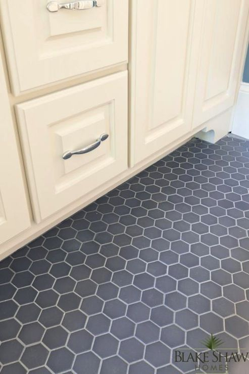 source: Blake Shaw Homes    Gorgeous detail shot of gray hexagonal tiled bathroom floors with creamy white raised panel bathroom vanity