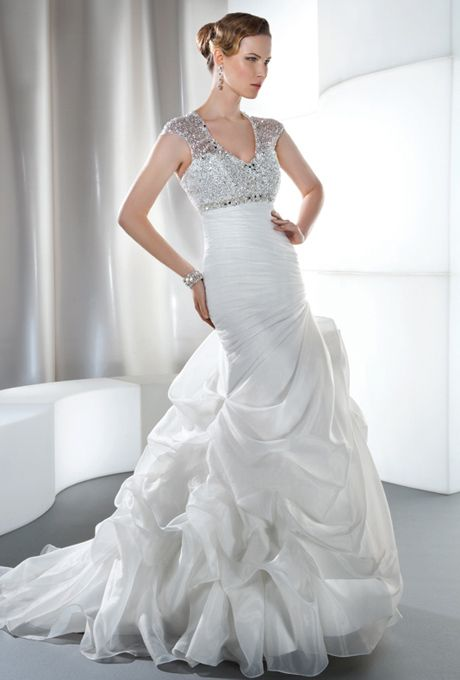 Brides: Demetrios - Illusions. Organza sleeveless, fit and flare with a V-neckline, asymmetrical ruching and bustled skirt. Empire bodice is embellished with beads and jeweling, and features a keyhole back finished with lace-up. Available in white, ivory, and diamond white.