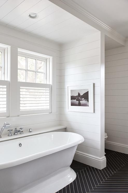 Thin black herringbone floor tiles finished with white grout contrasts a roll top freestanding bathtub placed in front of a ledge fitted with a polished nickel tub filler mounted beneath windows covered in white cafe shutters.