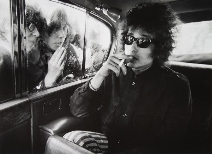 Bob Dylan relaxes in the back of a car.