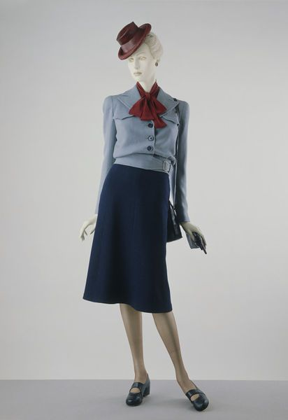 This is a good example of a Utility Suit. It is from the Utility Collection by the Incorporated Society of London Fashion Designers for the Board of Trade. It may have been designed by Victor Stiebel. The simplification and economy of material match the conditions laid down by the Board in relation to the manufacture of civilian clothing during the Second World War of 1939-1945.  The bloused jacket with square, padded shoulders closely resembles the battledress top of an army uniform. Via V.