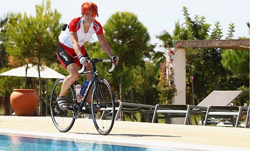 Auch die ehemalige Biathletin Kati Wilhelm kann nicht ohne Sport: Auf dem Fahrrad cruist sie am Pool entlang