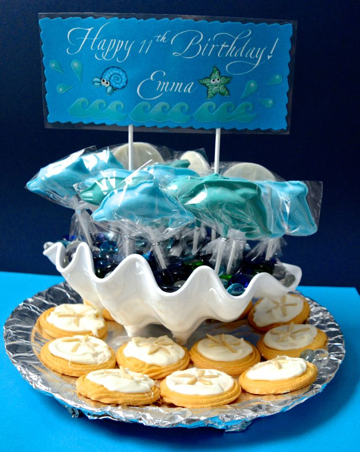 Chocolate Dolphin & Sand Dollar lollipops & Cookie Centerpiece   I made this centerpiece with lots of love for our grandaughter Emma's 11th beach theme birthday party. Homemade chocolate dolphin lollipops & sand dollar lollipops, sand dollar cookies in a seashell shaped bowl with glass stones & hand lettered sign.
