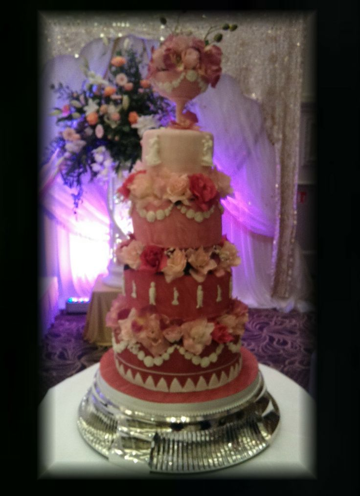4 Tier Marbled Pink Wedding Cake. Decorated with hand made sugar bowl, moulded sugar figures and silk flowers.