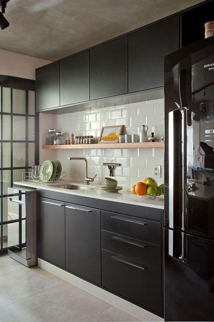 Decoração contemporânea com toque retrô e elementos industriais com ambientes integrados. Na cozinha parede de tijolinhos brancos e armario preto.