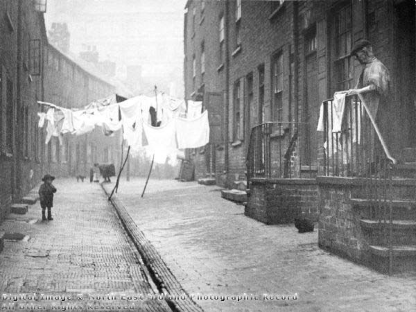 Red Lion Street (also known as Narrow Marsh), 1919.  Red Lion Street was the main street running east to west along the northern edge of the Narrow Marsh area. The wide windows on the top floors of the buildings (which allowed as much light as possible into the rooms) indicate that the original inhabitants were framework knitters or worked in the lace industry. Like Parrott's Place, Red Lion Street has a communal water pump and a drain.