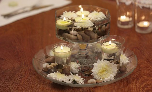table centerpiece with white mums, pebbles and floating candles