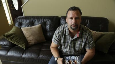 Retired U.S. Army Staff Sgt. Shawn Manning, at his home in Lacey, Wash., holds a photograph from a memorial for victims of a 2009 mass shooting at Ft. Hood, Texas. Manning, who still carries two bullets in his body from the shooting that killed 13 people, testified against Maj. Nidal Malik Hasan, the accused shooter.  The wait is nearly over | LA Times ~ August 20, 2013