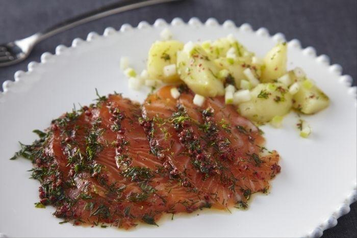 Une recette scandinave de saumon cru mariné servi avec une salade tiède de rattes et de pomme acidulée.