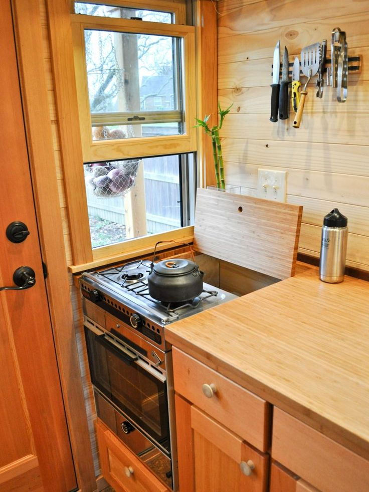 Full-size ranges, double-bowl sinks and side-by-side refrigerators simply won't fit. In their place: mini versions that don't hog space, such as this two-burner stove stacked on top of an oven (with storage tucked behind, to boot).