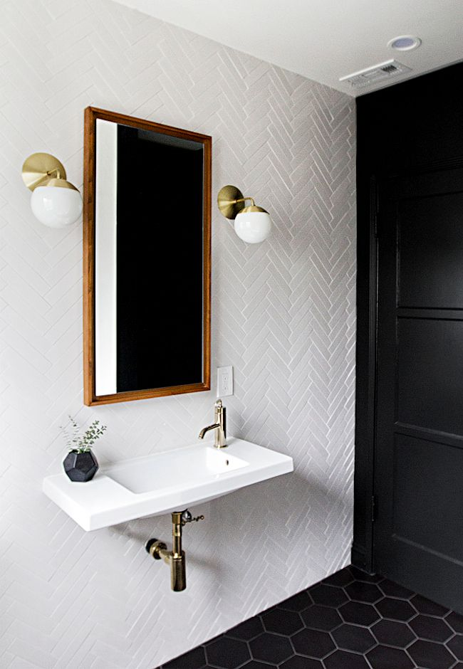An awesome bathroom redesign. Love the herringbone subway tile contrasted with the black hexagonal tiles and black wall paint.The brass fixtures are a great touch, as is the unexpected warmth of the wooden mirror frame.