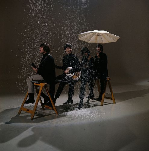 The Beatles sitting on a trestle under a simulated snow shower during the making of 'I Feel Fine', 1965.