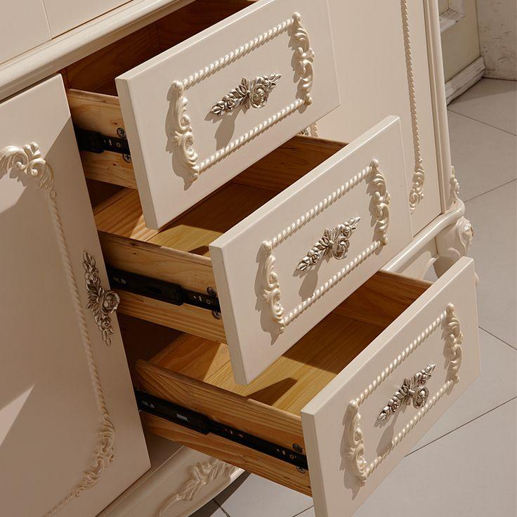 Выдвижные ящики внизу книжного шкафа с резьбой по дереву и металлическими ручками