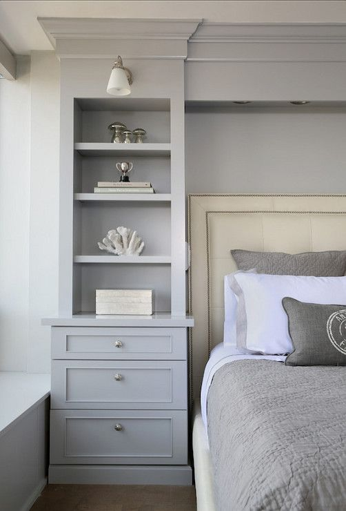 gorgeous bedroom boasts gray builtin bookcase with lower drawers accented with round brushed nickel