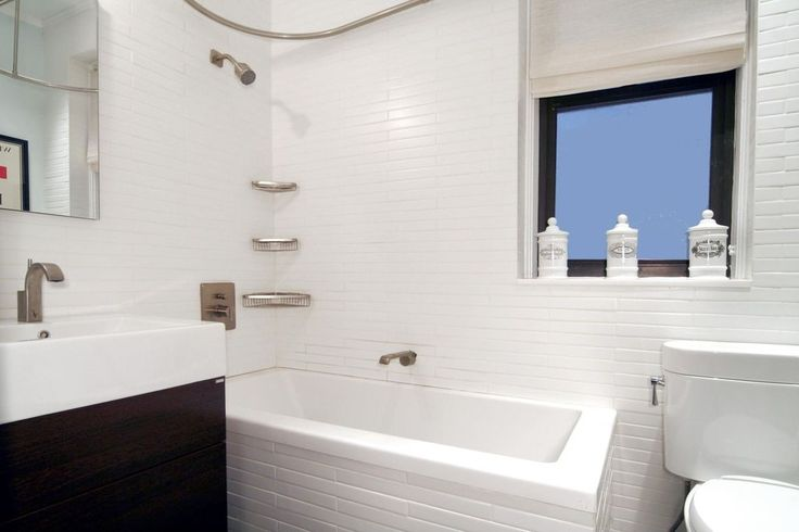 Subway white porcelain tiles brighten up the small space of this bathroom with a textured look.