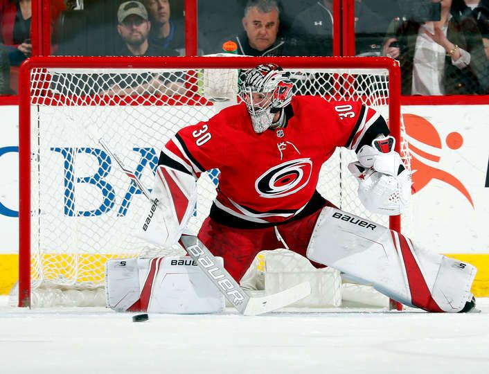 RALEIGH, NC - FEBRUARY 23: Cam Ward #30 of the Carolina Hurricanes watches as a Pittsburgh Penguins shot attempt goes wide of the net during an NHL game on February 23 2018 at PNC Arena in Raleigh, North Carolina. (Photo by Karl DeBlaker/NHLI via Getty Images)