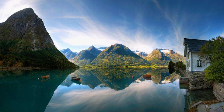 Auf Fotos zeigt sich Fjord Norwegen als eine Region voller atemberaubender Landschaften: mit tiefblauen Fjorden, fließenden Wasserfällen und steilen, schneebedeckten Bergen, die hoch aus dem Wasser ragen.