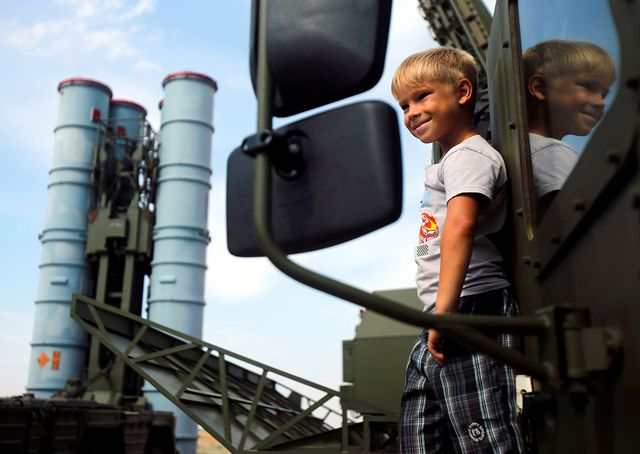 A boy stands on the S-300 air defence mobile missile system during the International Army Games 2016 at the Ashuluk military polygon outside of Astrakhan, Russia. [Reuters]