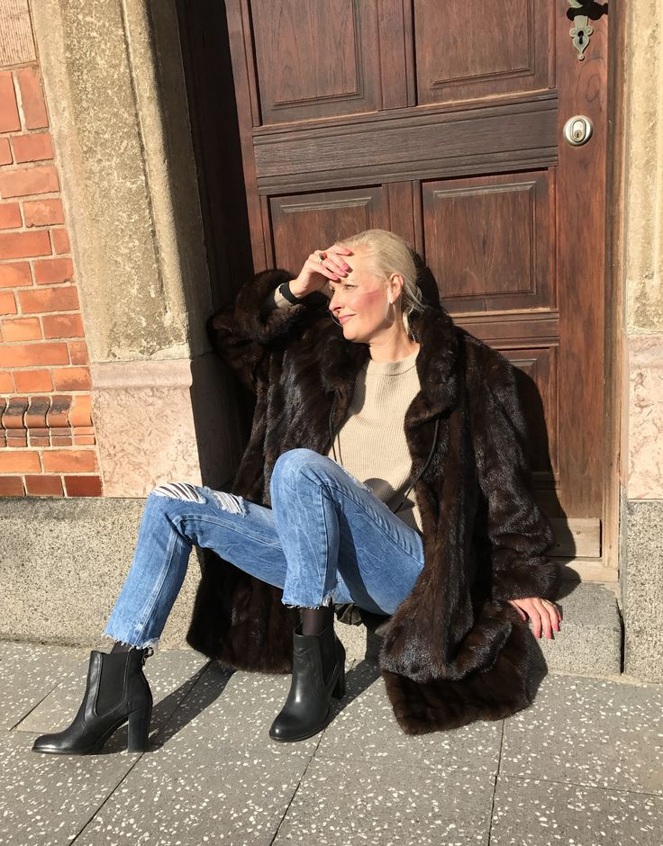 A moment with sun in the cold Scandinavia. In a fur with jeans and a pair of boots and a cozy sweater.