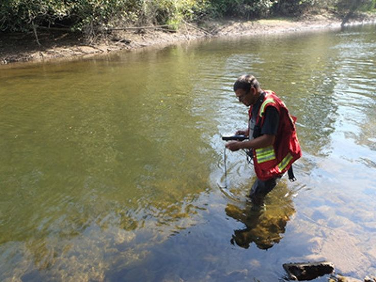 A Coquitlam environmental services officer tests water quality in the Coquitlam…