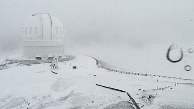 Parts of the US state of Hawaii have received a winter weather warning, with up to three feet (90cm) of snow over the past few days. A telescope on the summit of Mauna Kea on Hawaii's Big Island is covered in snow (01 December 2016)