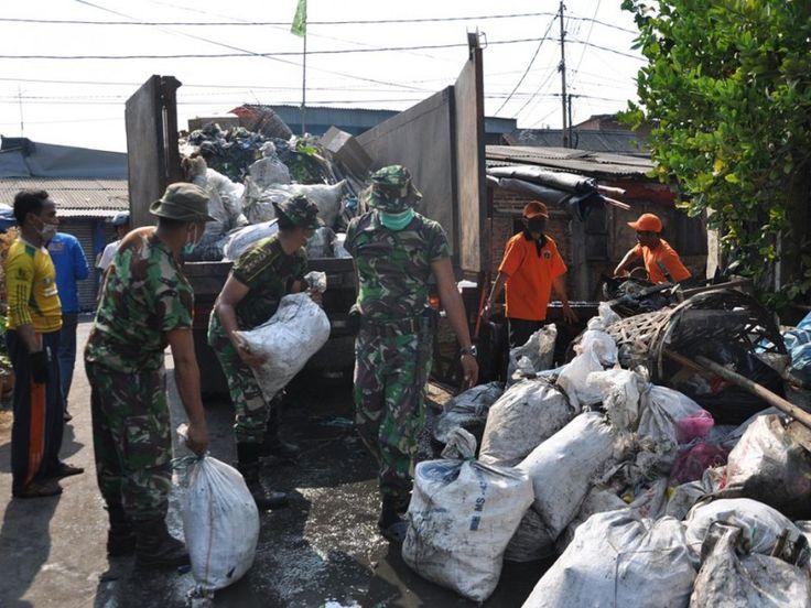 Anggota TNI memasukkan sampah ke dalam