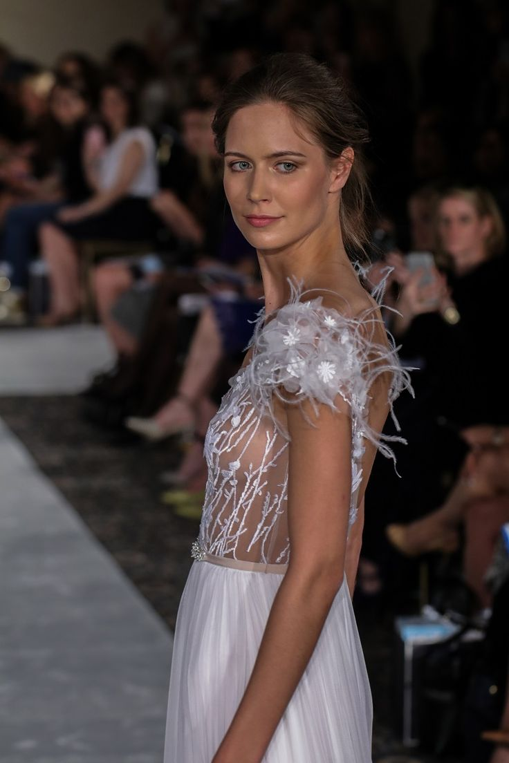 Deep V-neck gown with silk chiffon skirt- bodice with branch embroidery and feather shoulders. Color: White