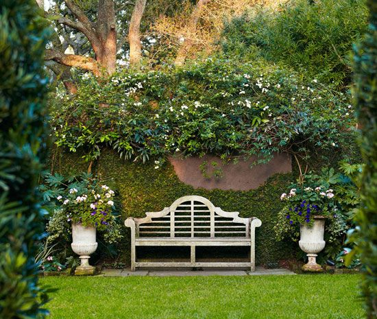 A Lutyens-style bench is flanked by graceful urns before brick-and-stucco walls - Traditional Home®  Photo: Brie Williams