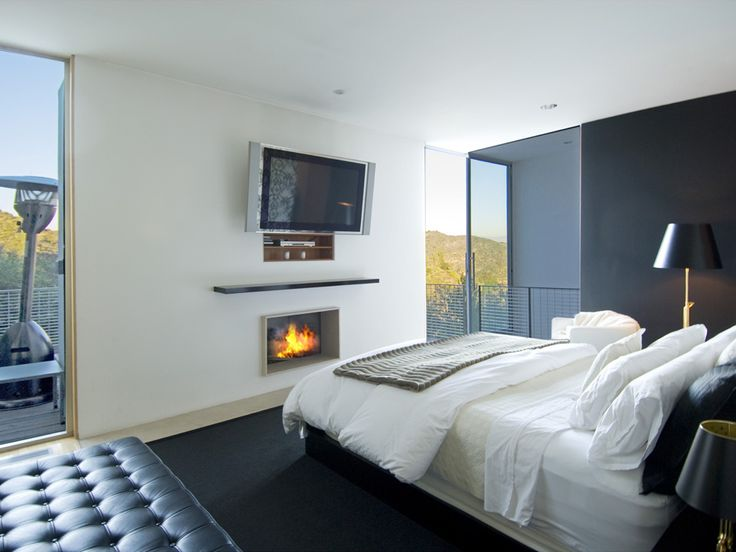 Luxury Bedroom Design With Black And White Bed Color Scheme Above The Carpets Have A Modern Fireplace Under LCD TV