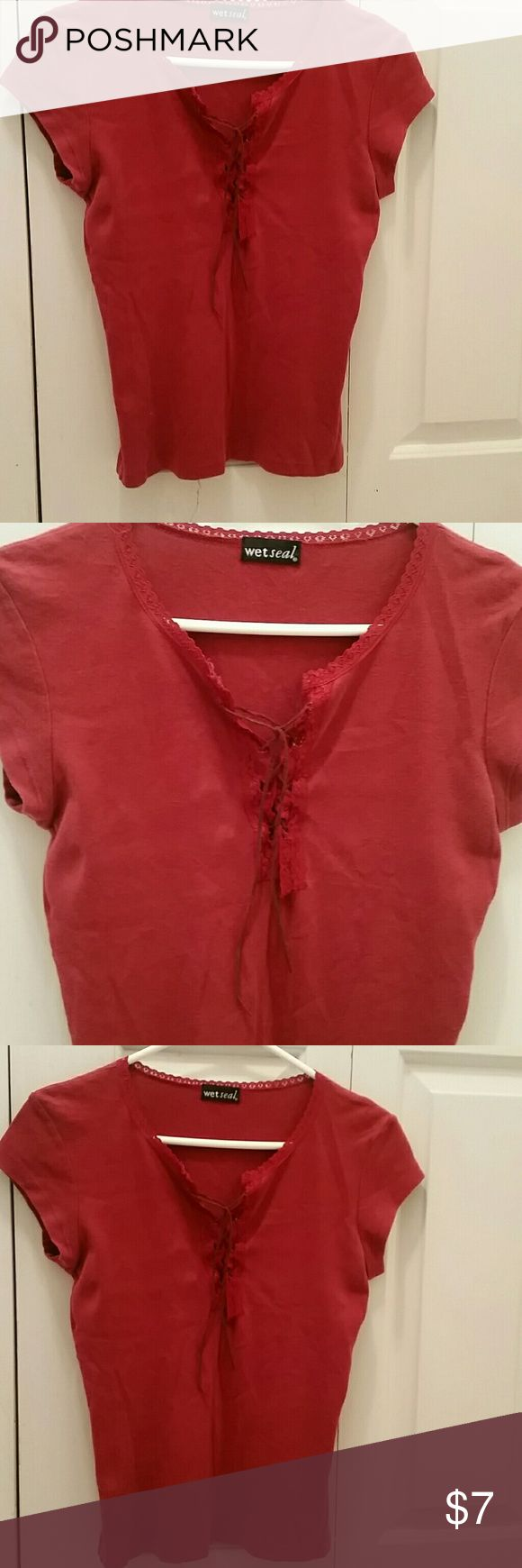 VERY SEXY TEE!   PICS DO NOT DO JUSTICE!   The red Wet Seal t-shirt will easily fit any woman from a size medium to size large. It is absolutely precious and very sexy with its  laced lined neck and sleeves as well as in the middle, where, I tried to show with pictures, it laces up with leather that is trimmed in lace, as well. The shirt is way too cute! Just too big Wet Seal Tops Tees - Short Sleeve