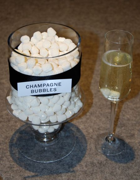 Champagne bubble candy served alongside a glass of champagne.  See more candy wedding favors and party ideas at www.one-stop-party-ideas.com