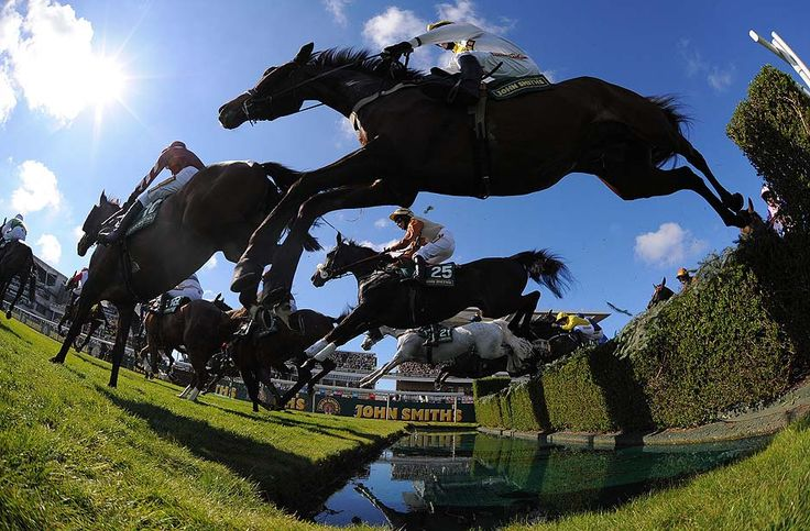 Liverpool, England — Unowatimeen, ridden by Samantha Drake, center, jumps the water jump during the Fox Hunters Steeplechase during the first day of the Grand National horse racing meeting at Aintree Racecourse. The meeting culminates in the Grand National on Saturday, which is run over a distance of four miles and four furlongs (7,242 meters), and is the biggest betting race in the United Kingdom.    PHOTOGRAPH BY: ANDREW YATES