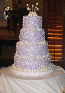 Four tier round wedding cake with white icing in the shape of lovely scrolls decorating the tiers. Pretty pearl cake topper and small pearls decorating the base of each tier.