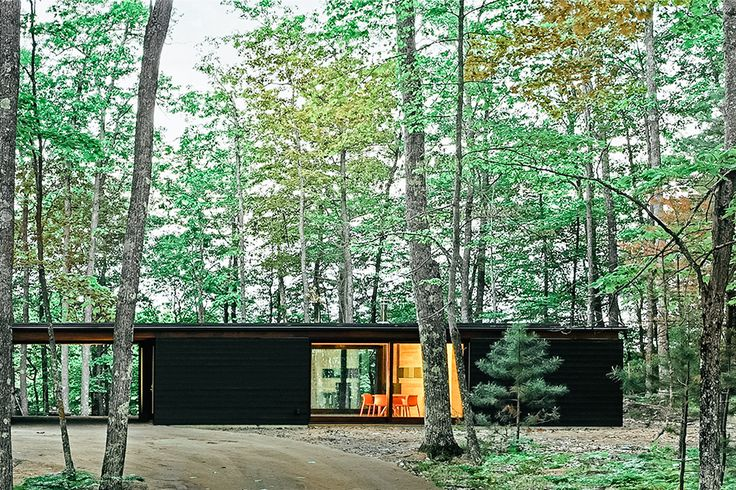 Overlooking a lake in the Wisconsin backwoods, the Linear Cabin gets its name from its continuous layout. The home consists of three blackened pine-clad forms, separated by two openings. Each box has a different function - storage, sleeping, and service...