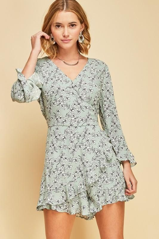 f79a29dd798a Floral print wrap romper featuring ruffle details at sleeves and hem. Snap  button closure at bust. Key hole button and self tie ribbon closure at back.