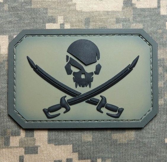 Sleek PVC Skull and Swords #Velcro_Patch - Make a bold statement with this modern take on the age-old pirate symbol! Goes great on #military-style_clothing, especially camouflage #jackets. Can be easily removed thanks to the hook velcro added to the rear side. Choose from a variety of colors, including solid and camo.