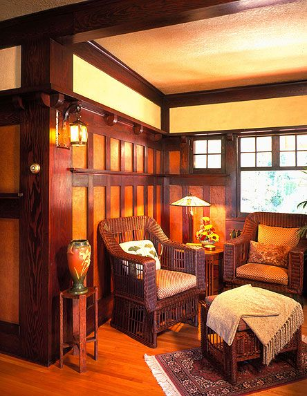 Sitting room/den with wicker furniture in the Arts & Crafts- Mission style. Love the wainscoting, plate rail and pop of orange.