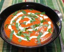 Sopa cremosa de tomate rojo adornado con crema y albahaca picada.