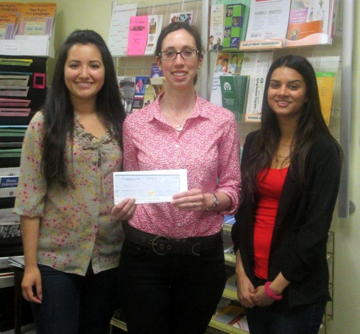 Emily Sward (C) of Junior League Toronto presents a Healthy Living grant to Priscilla and Rebecca, staff of our Building Strong Futures: Young Women's Outreach
